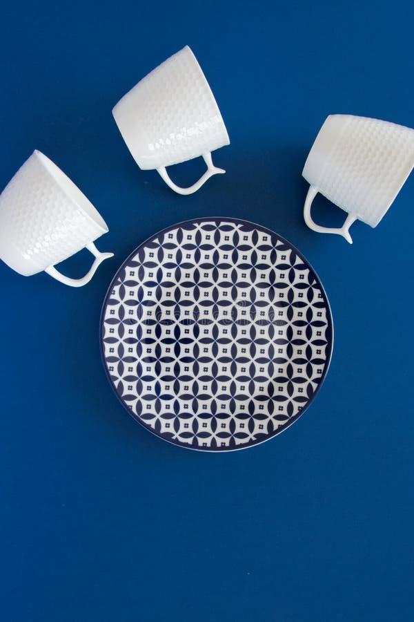 Vista puesta plana de arriba de las tazas de la placa limpia del vajilla y del café con leche en fondo azul marino foto de archivo
