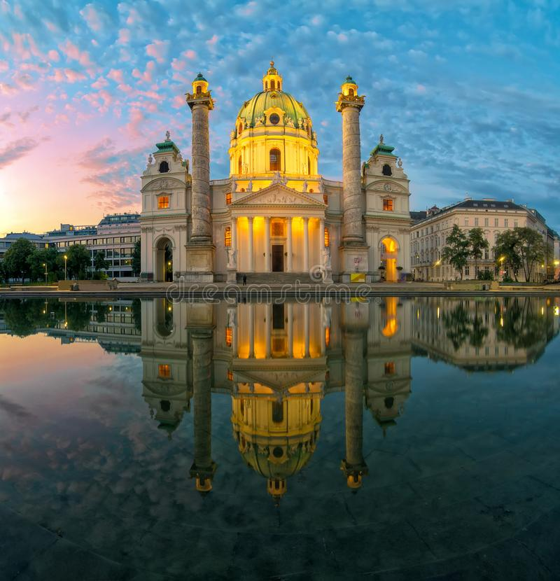 Vista que sorprende de Karlskirche con la iluminaci?n y la reflexi?n en el agua, Viena, Austria fotos de archivo