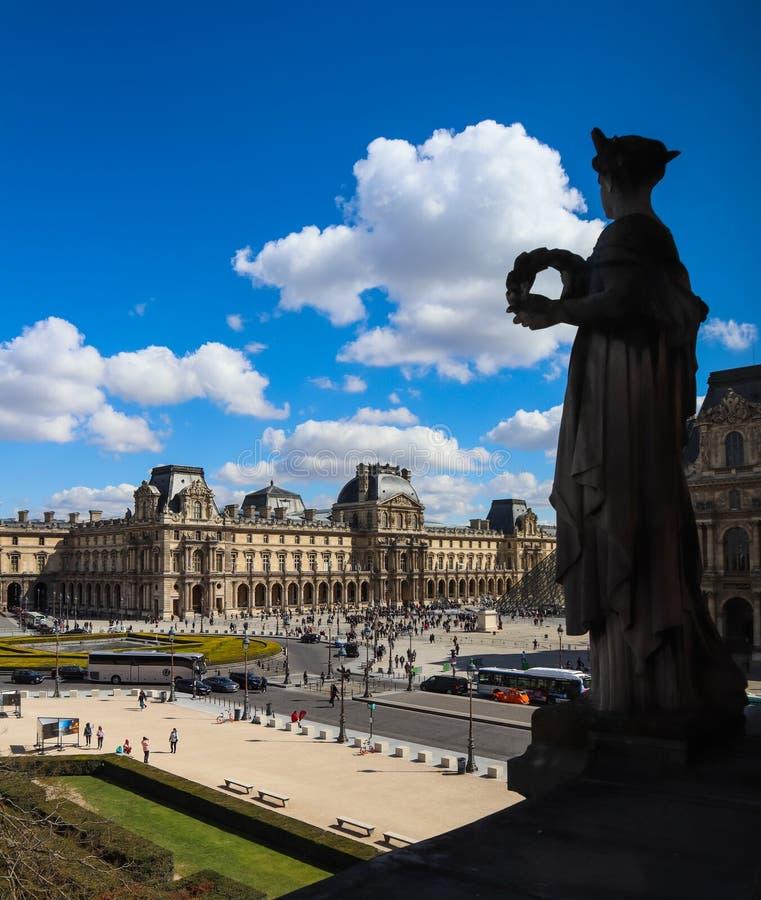 Vista que sorprende del cuadrado de la ventana del Louvre y de la silueta de la escultura en frente imágenes de archivo libres de regalías