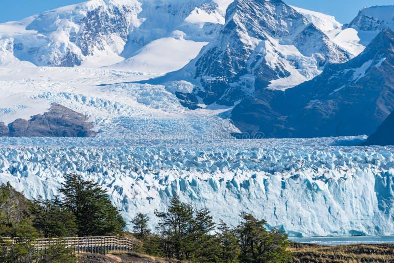 Vista que sorprende del glaciar de Perito Moreno, glaciar azul del burg del hielo del pico de la montaña a través del lago azul d imagenes de archivo