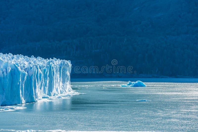 Vista que sorprende del glaciar de Perito Moreno, glaciar azul del burg del hielo del pico de la monta?a a trav?s del lago azul d foto de archivo