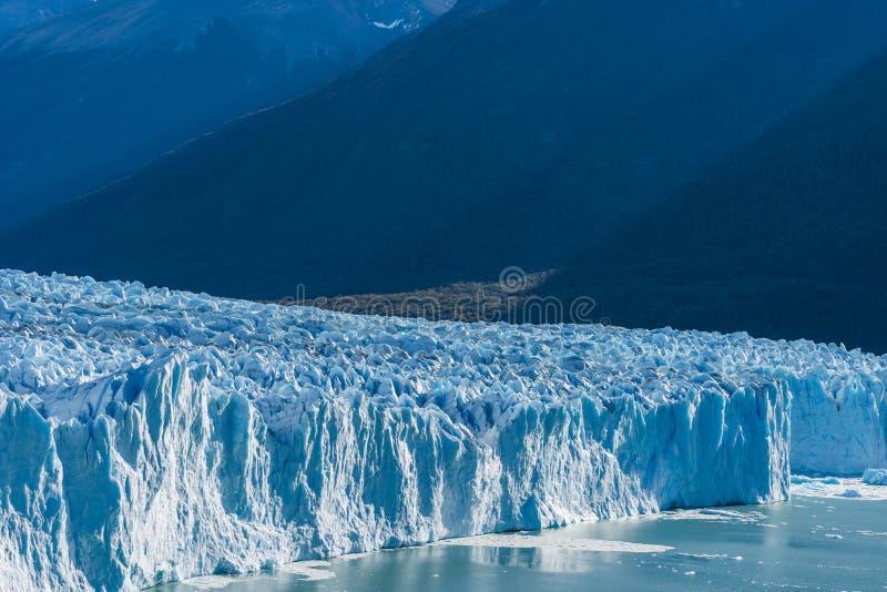 Vista que sorprende del glaciar de Perito Moreno, glaciar azul del burg del hielo del pico de la monta?a a trav?s del lago azul d foto de archivo libre de regalías
