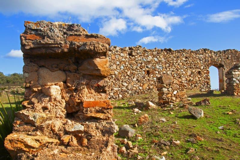 Vista ravvicinata del vecchio muro rovinato con porta aracchiata sul campo verde Il giorno dell'autunno a Siviglia, Spagna immagine stock