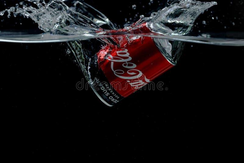 Vista ravvicinata della lattina che cade in acqua Coca Cola fotografia stock