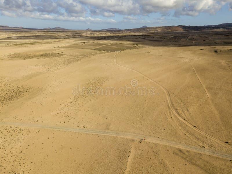 Vista a?rea de un paisaje del desierto en la isla de Lanzarote, islas Canarias, Espa?a Un hombre con una camisa anaranjada que ca fotografía de archivo libre de regalías