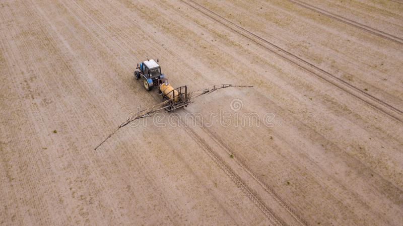 Vista a?rea del tractor de cultivo que ara y que roc?a en campo foto de archivo libre de regalías
