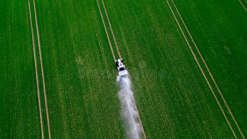 Vista a?rea del tractor que roc?a las sustancias qu?micas en el campo verde grande fotos de archivo