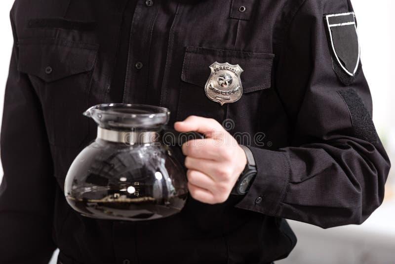 vista recortada do policial segurando panela de vidro imagem de stock