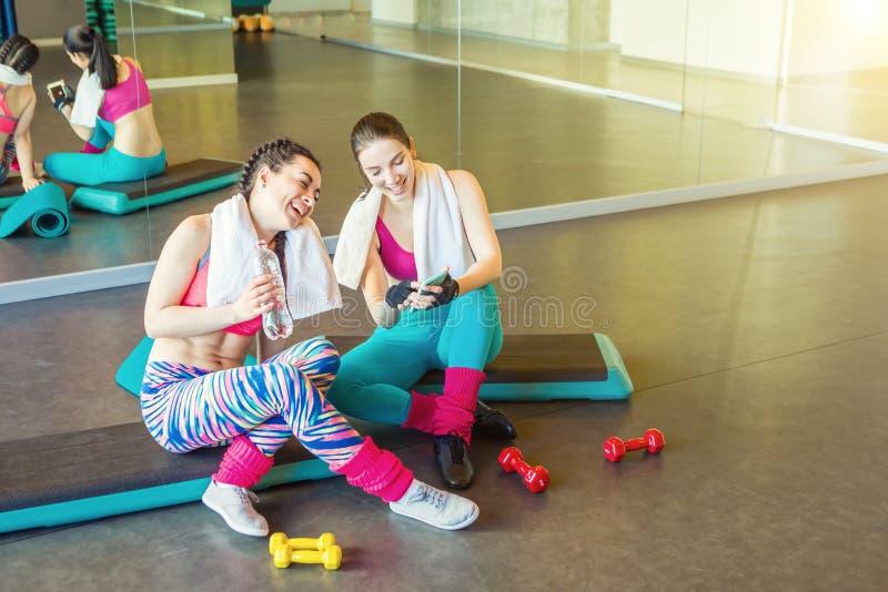 Vista relaxado e rindo da mulher de dois amigos ao telefone após a formação ativa dos esportes imagens de stock royalty free