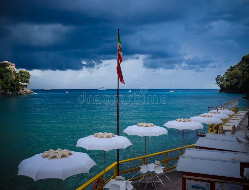 Vista sbalorditiva degli ombrelli e del mare prima della tempesta vicino a Portofino in Italia immagine stock