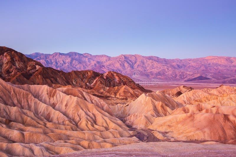 Vista scenica dal punto di Zabriskie, mostrante gli avvolgimenti, i contrasti di colore e struttura nella roccia erosa all'alba,  fotografia stock