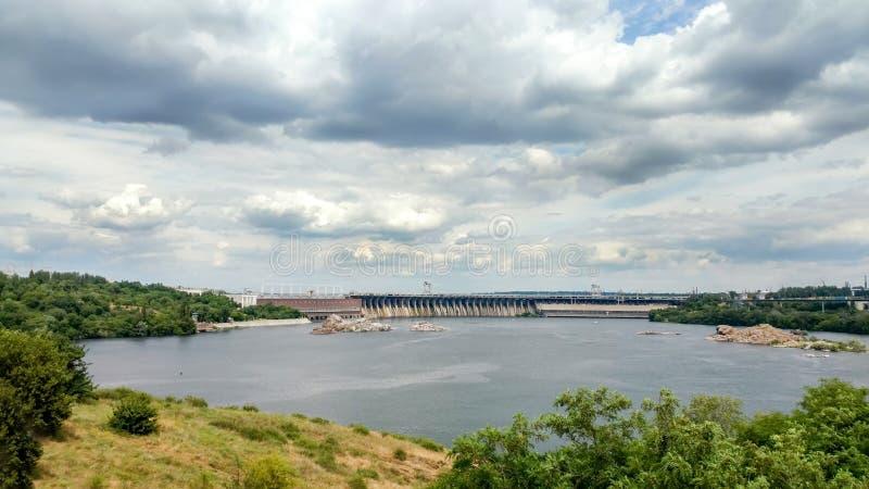 Vista scenica dall'isola di Khortytsia al fiume di Dnieper, al cielo nuvoloso drammatico ed alla diga della centrale elettrica di fotografia stock