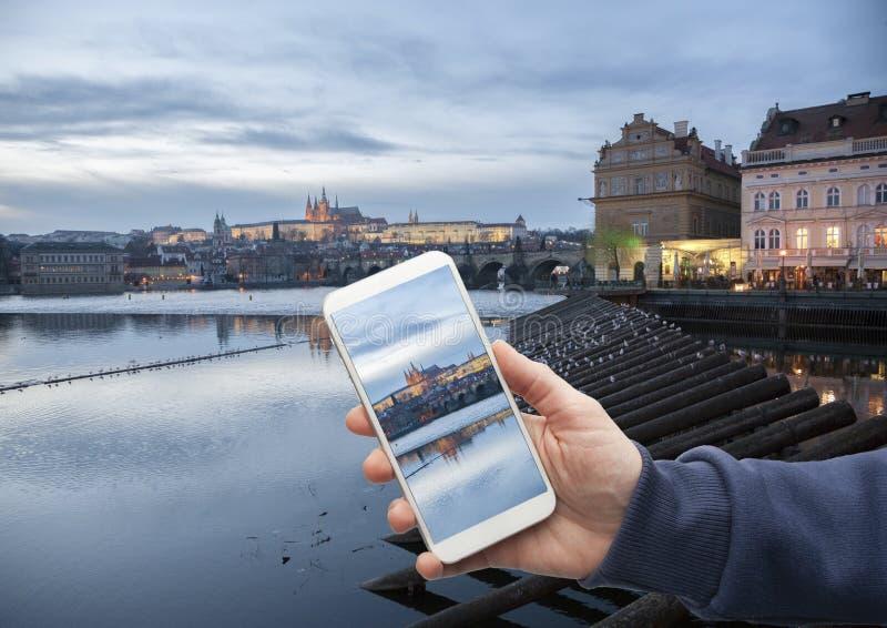 Vista scenica del centro storico Praga, del ponte di Charles e delle costruzioni di vecchia mano della città con uno smartphone,  immagini stock libere da diritti