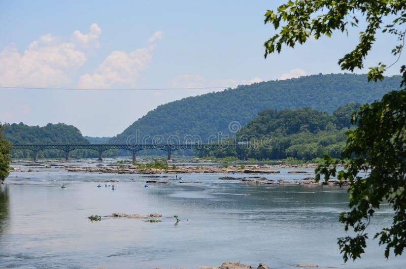Vista scenica del fiume Potomac, con la gente che bighellona sui galleggianti pigri della tubatura del fiume nell'acqua un giorno fotografia stock libera da diritti
