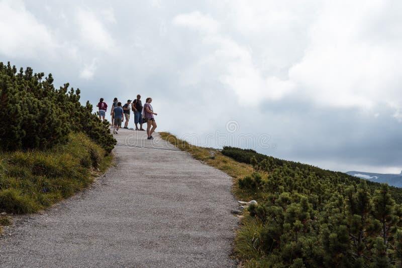 Vista scenica del percorso nella montagna con la gente che fa un'escursione sul backgr fotografia stock libera da diritti