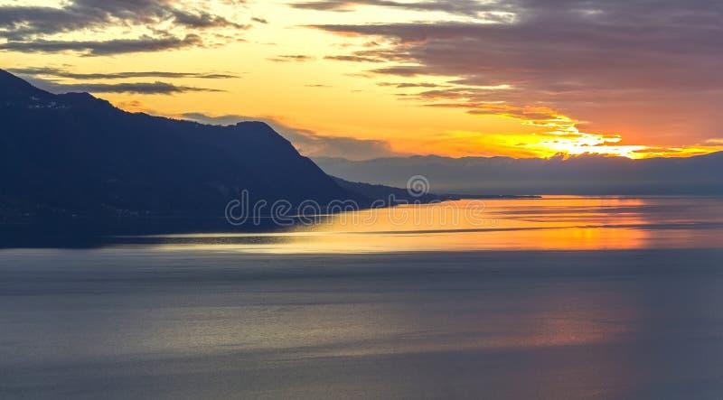 Vista scenica del tramonto sopra il lago Leman con il cielo giallo con le nuvole e le montagne delle alpi nel fondo, Montreux, Sv fotografia stock
