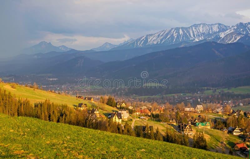 Vista scenica del villaggio di Koscielisko con panorama di alto Tatras su fondo, Polonia fotografie stock