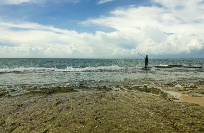 Vista scenica della spiaggia rocciosa con la siluetta dell'uomo nella pesca di orizzonte con la barretta rilassata alla bella spi immagine stock libera da diritti