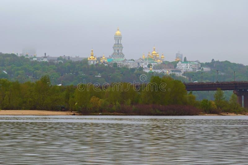 Vista scenica di mattina del fiume di Dnipro, colline verdi con Kiev antica Pechersk Lavra Paesaggio nebbioso misterioso della mo immagini stock