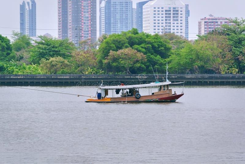 Vista scenica di piccola barca di rimorchio che tira l'altra barca con la corda contro gli alberi ed il paesaggio urbano fotografia stock