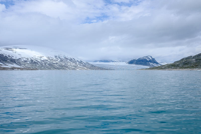 Vista scenica di Styggevatnet con le montagne nevose sui precedenti fotografia stock