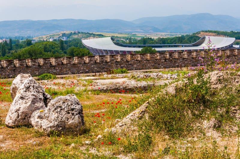 Vista scenica sullo stadio moderno a Skopje che ha chiamato Philip II arena nazionale con terra rocciosa pieno del terreno comuna immagini stock