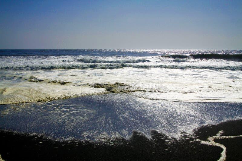 Vista sobre a ressaca de formação de espuma branca da água da praia preta vulcânica da areia que brilha em nivelar o sol no horiz imagens de stock royalty free