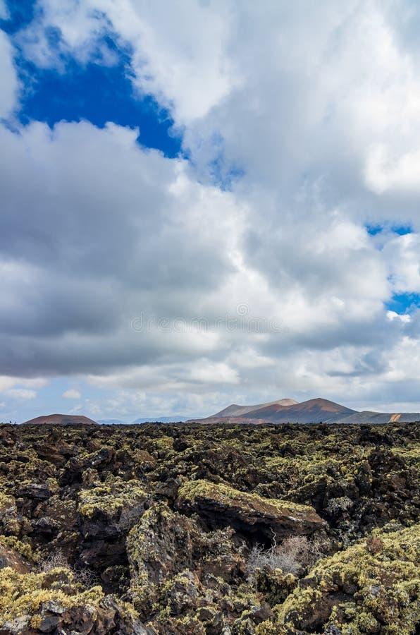 Vista sobre um campo de lava em Lanzarote com os vulcões no fundo fotos de stock royalty free