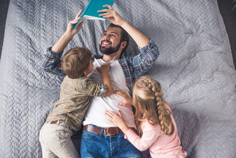 vista sopraelevata del libro di lettura del padre a wile dei bambini che si trova sul letto fotografia stock