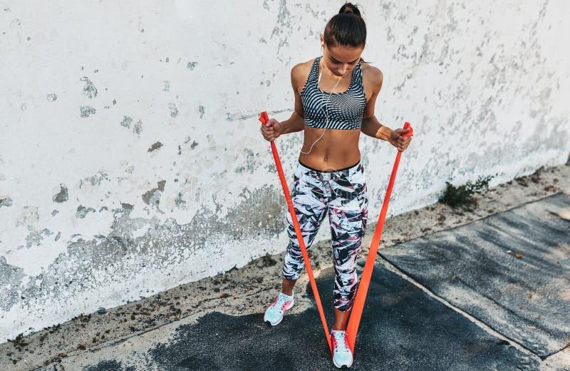 Vista sopraelevata della condizione della donna di forma fisica contro il muro di cemento che fa allungando gli esercizi che teng fotografia stock libera da diritti