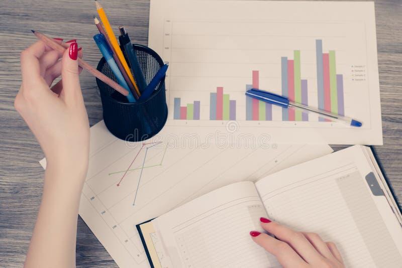 Vista sopraelevata della mano del ` s della donna che prende una matita dal supporto per la penna fotografia stock