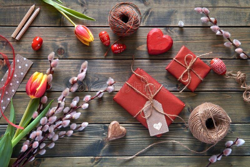 Vista sopraelevata della tavola di legno con le decorazioni di primavera, wrapp fotografia stock