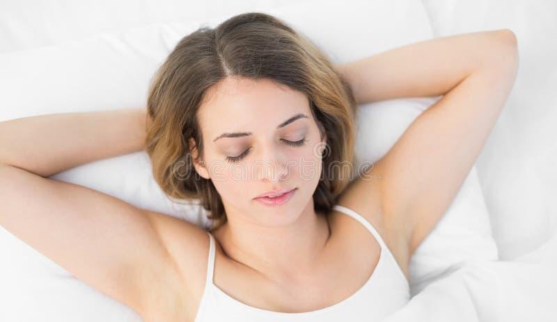 Vista sopraelevata di menzogne abbastanza calma di sonno della donna sul suo letto fotografia stock libera da diritti