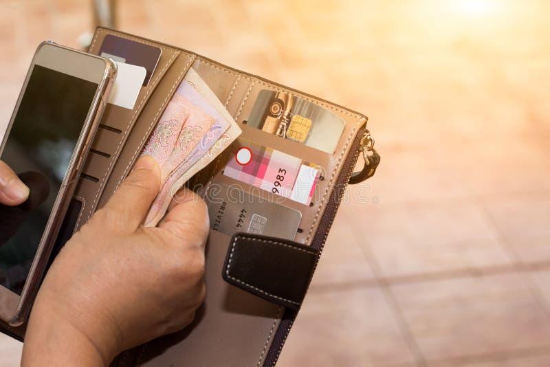 Vista sparata potata delle mani femminili che selezionano le carte di credito dal suo portafoglio fotografia stock libera da diritti