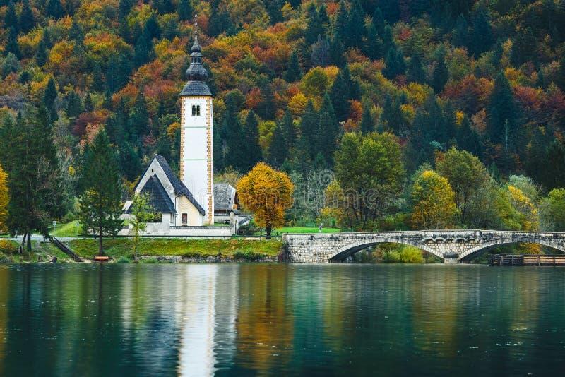 Vista splendida della scena autunnale variopinta della chiesa famosa di St John il battista, lago Bohinj, Ribicev Laz, villaggio  fotografia stock