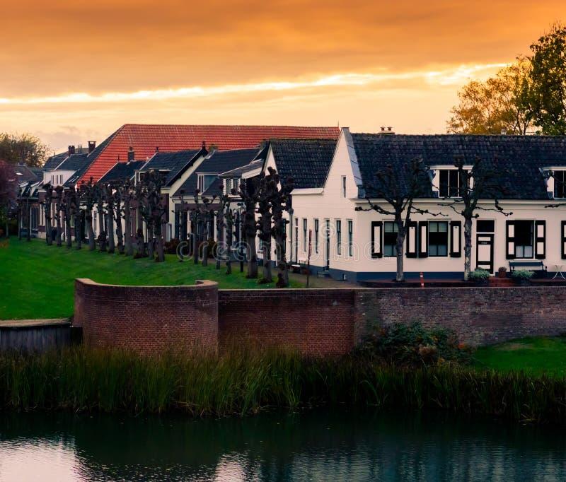 Vista su alcune case moderne con acqua ed erba al tramonto nella città Leerdam la vicinanza olandese olandese e tipica immagine stock libera da diritti
