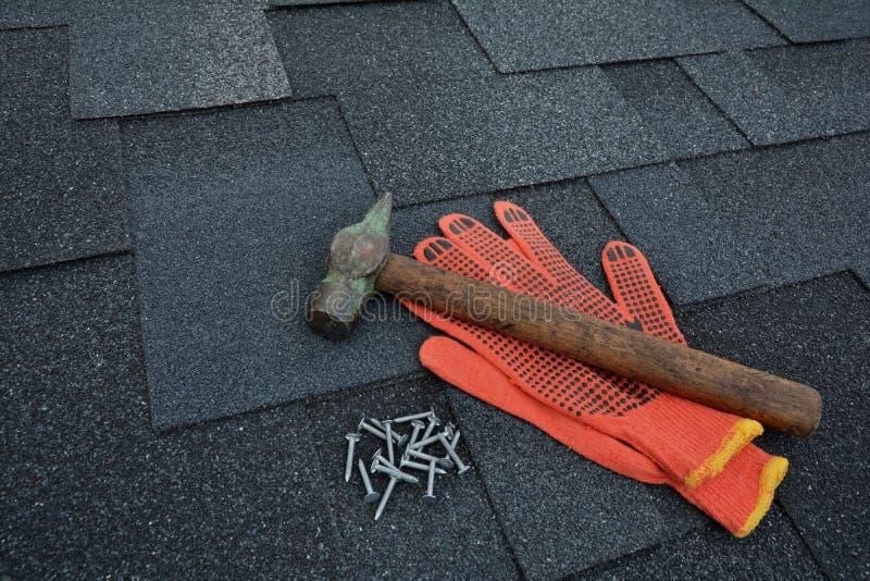 Vista su Asphalt Roofing Shingles Background Assicelle del tetto - tetto Asphalt Roofing Shingles Hammer, guanti e chiodi immagine stock libera da diritti