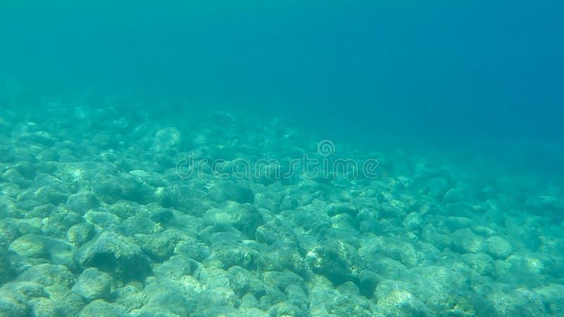 Vista SUBACQUEA dell'acqua della radura del turchese e dei ciottoli bianchi sparsi fuori dal fondale marino della baia di Antisam fotografia stock