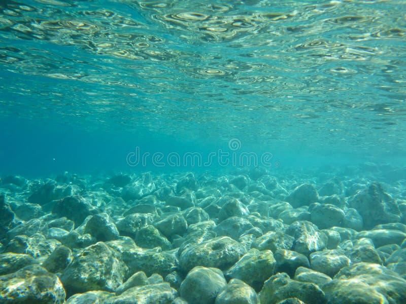Vista SUBACQUEA dell'acqua della radura del turchese e dei ciottoli bianchi sparsi fuori dal fondale marino della baia di Antisam fotografie stock libere da diritti