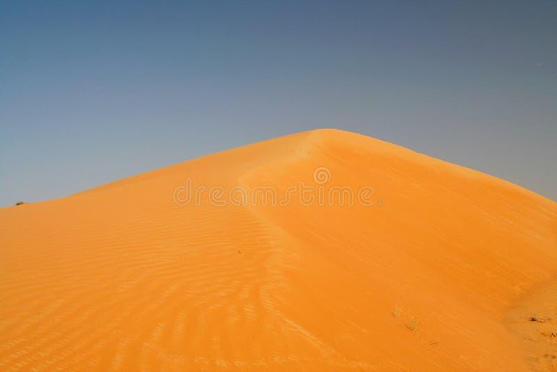 Vista sul cono isolato della duna di sabbia arancio rossa contro cielo blu fotografie stock