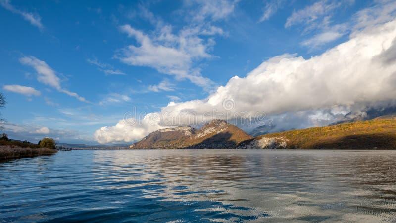 Vista sul lago Annecy, Francia, con le montagne di belle nuvole nei precedenti fotografia stock libera da diritti