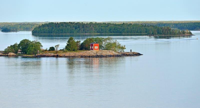 Vista sul mare Casa di legno rossa sull'isola verde in Mar Baltico fotografia stock libera da diritti