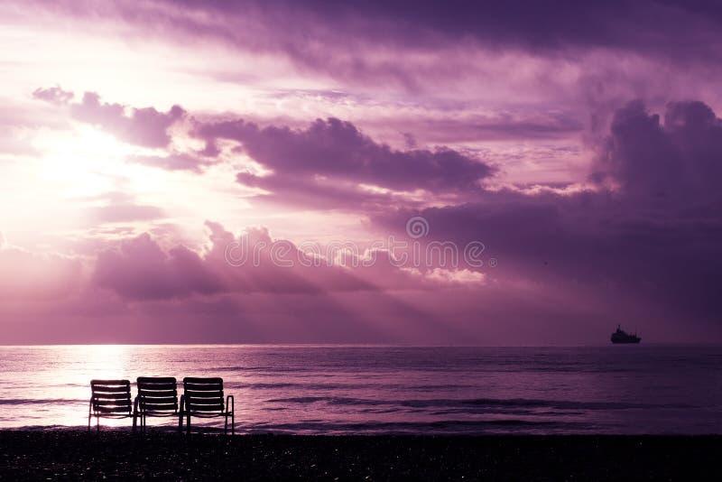 Vista sul mare con i raggi luminosi celesti e tre sedie sulla spiaggia a Larnaca immagine stock