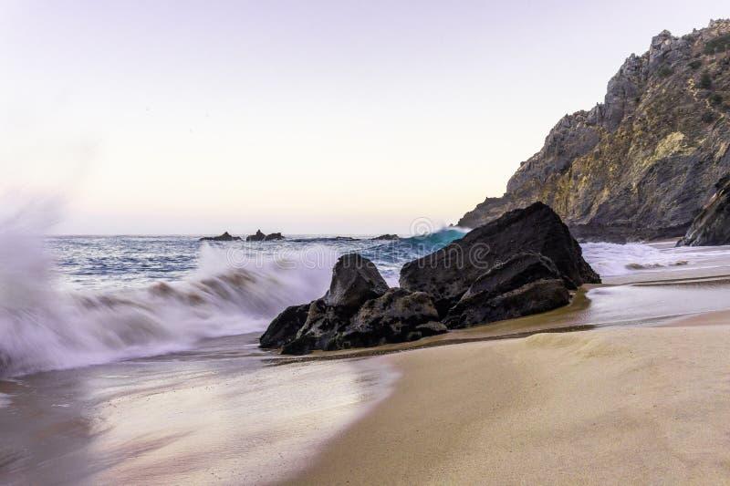Vista sul mare con l'oceano nel moto al tramonto in spiaggia sabbiosa di Adraga immagini stock