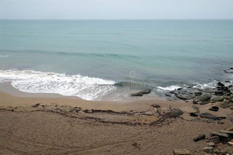 Vista sul mare con la spiaggia e la spuma vuote del mare il giorno nuvoloso fotografie stock libere da diritti