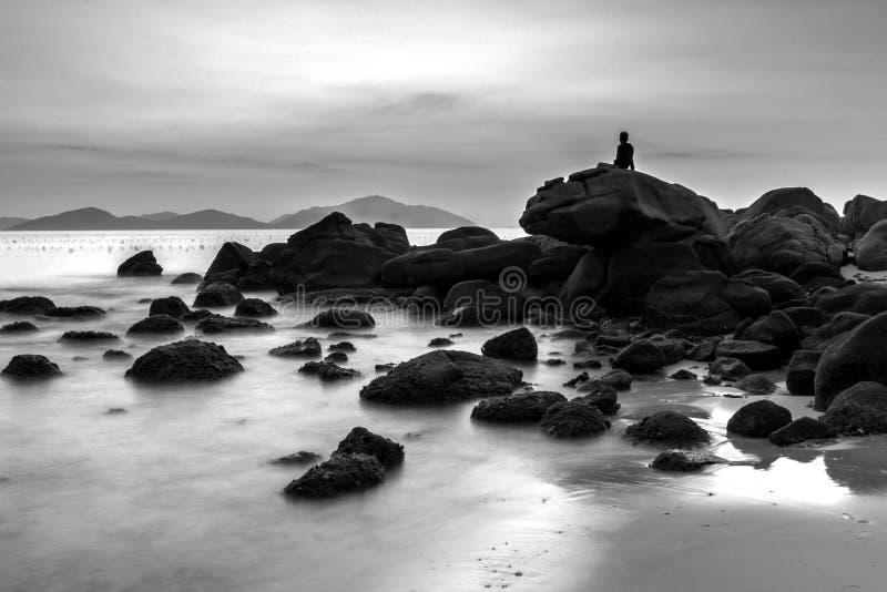 Vista sul mare con un uomo solo che si siede sui massi alla spiaggia immagini stock