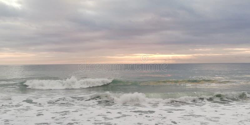 Vista sul mare di tramonto Il sole attraversa le nuvole pesanti basse immagine stock