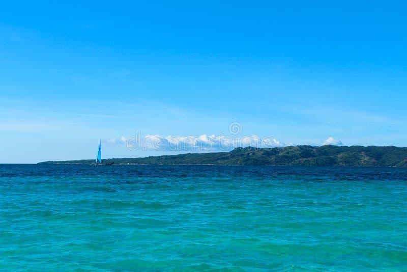Vista sul mare e una barca a vela immagine stock