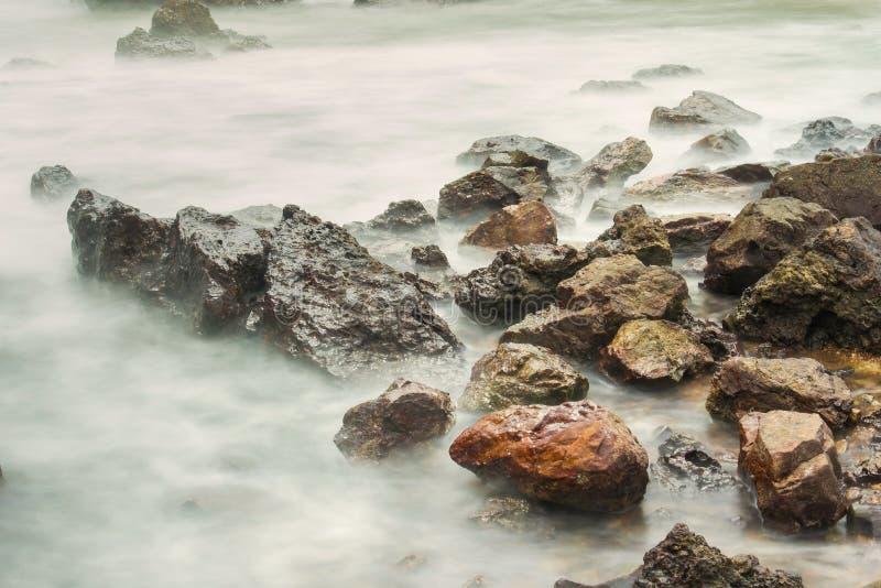 Vista sul mare lunga di esposizione con le onde spumose che spruzzano contro una roccia fotografia stock