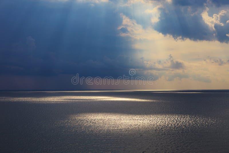 Vista sul mare nuvolosa dopo la tempesta che vede i raggi di sole naturali al tramonto fotografia stock libera da diritti